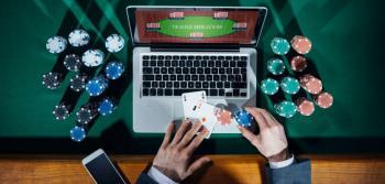 Laptop med Texas Hold'em samt händer som håller kort och spelmarker och en mobil bredvid.